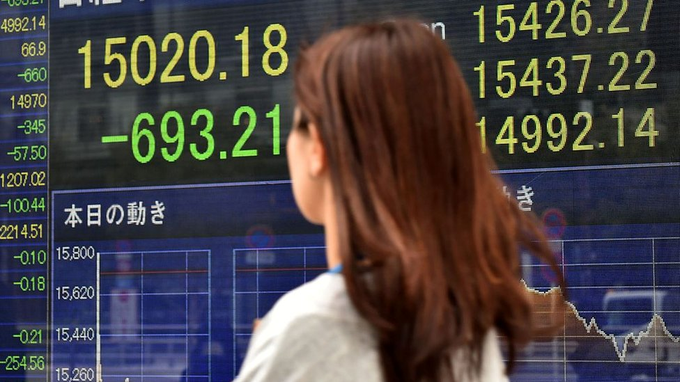 A pedestrian walks past a share prices board showing numbers of the Tokyo Stock Exchange in Tokyo on February 12, 2016