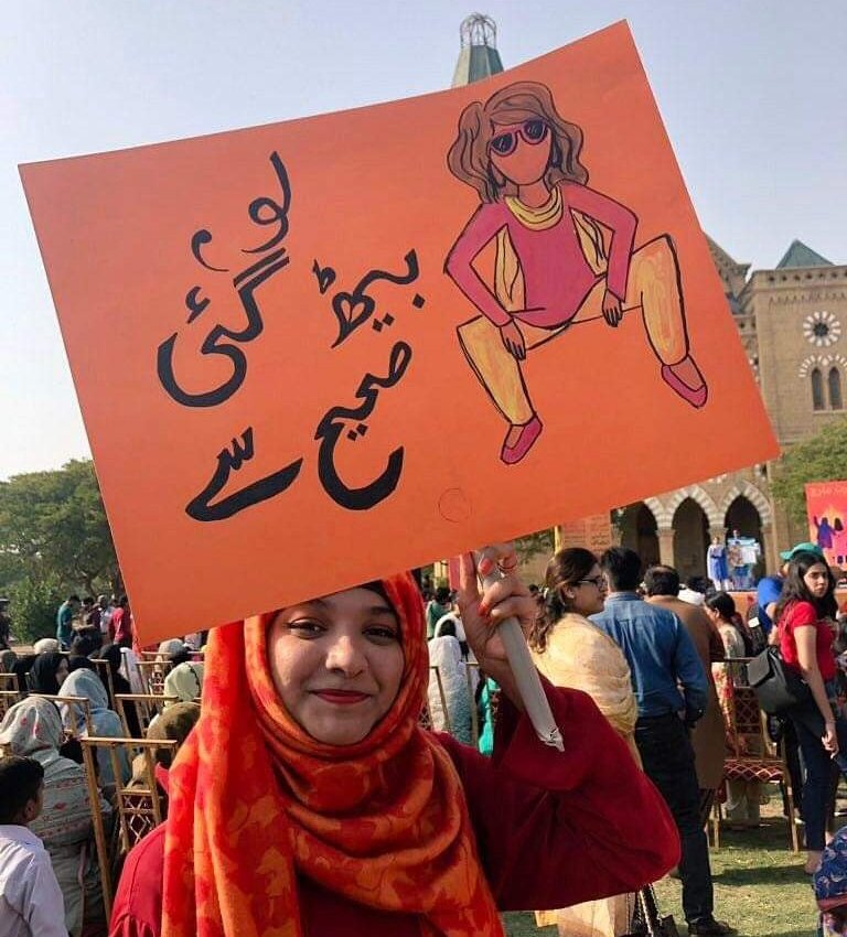"Rashida holding the ""womanspreading placard"""