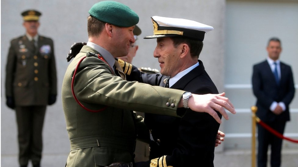 A UK and Spanish naval officer embrace at a ceremony of transfer of authority of the leadership from UK to Spain of European Union Operation Atalanta on 29 March 2019