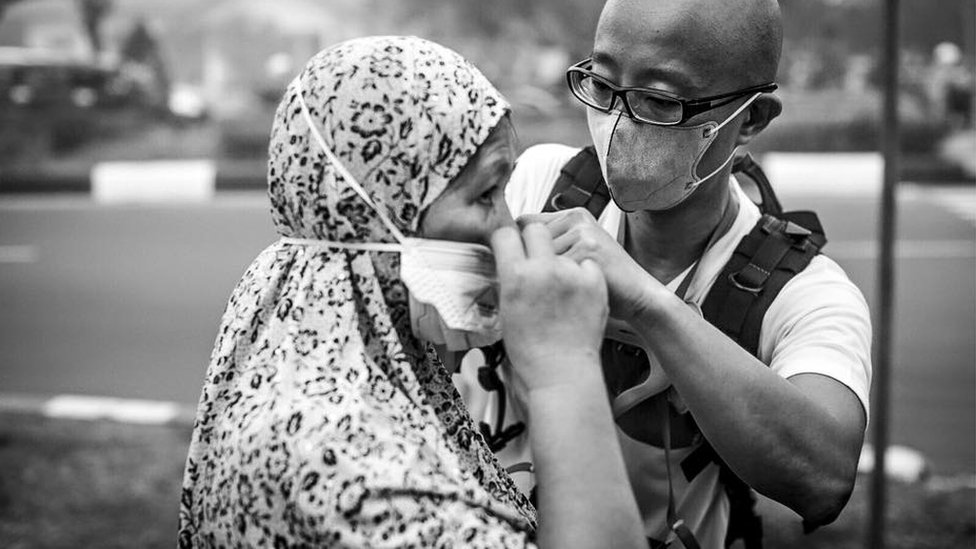 A volunteer helps a woman in Indonesia's Kalimantan province to put on a specialised N95 mask