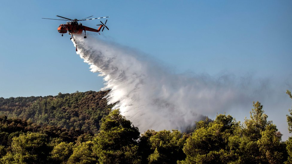 A firefighting helicopter dropping water over a forest to calm the flames