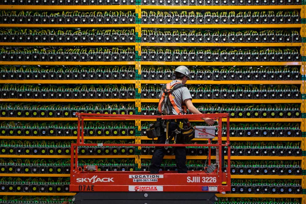 A technician inspects computers mining bitcoin in Quebec