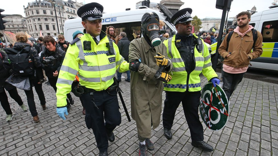 A protester wearing a gasmask and boiler suit with police