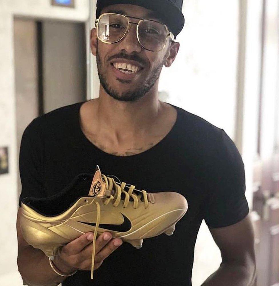 Pierre-Emerick Aubameyang holding a football boot