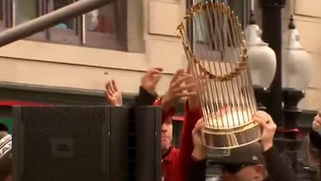 Boston Red Sox fan hits World Series trophy with beer can