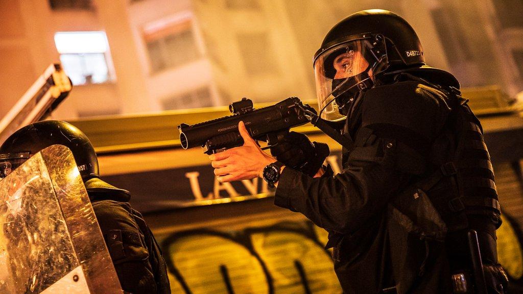 Un policía apunta con su arma de proyectiles de goma.