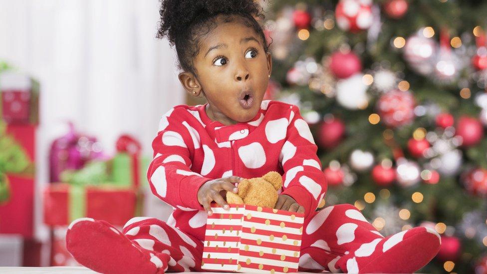 Una niña sorprendida con un regalo.