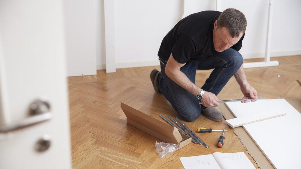 Hombre leyendo instrucciones para armar un mueble