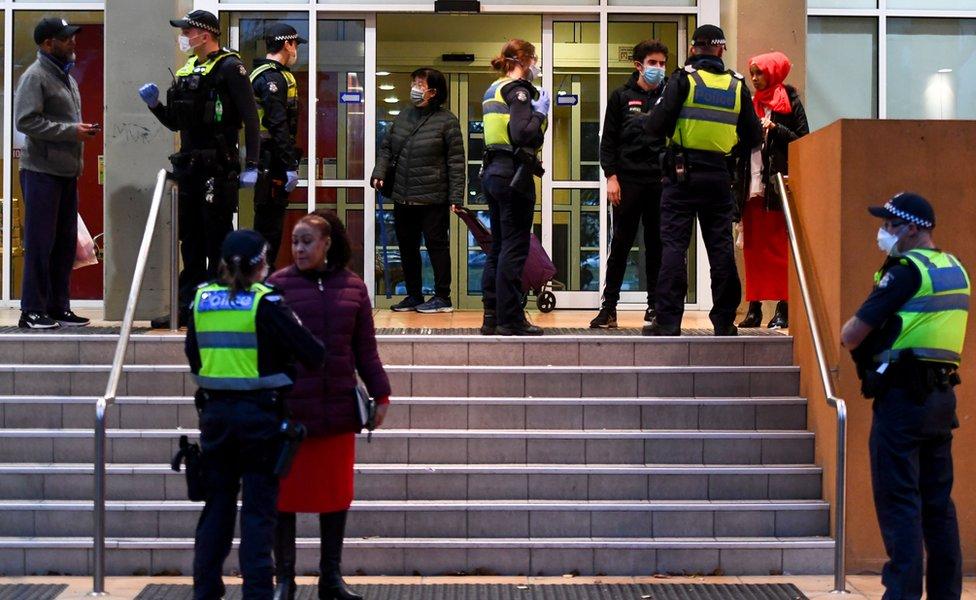 Policiais falando com os moradores do lado de fora da entrada de um dos blocos de apartamentos