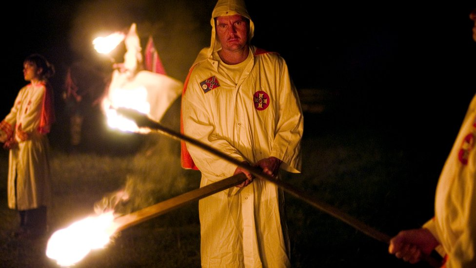 Ku Klux Klan members light torches as they begin a cross-lighting ceremony at the White Heritage Days Festival in Alabama in 2004.