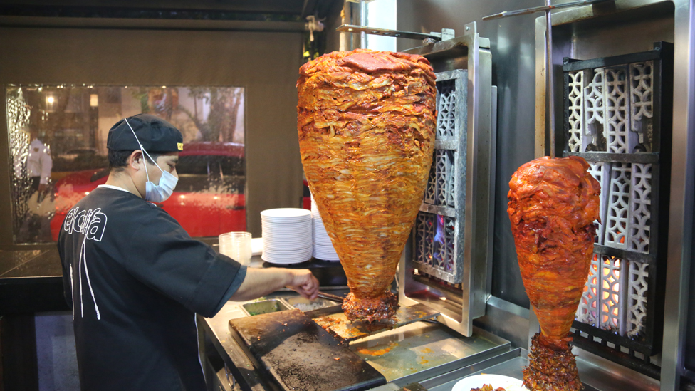 Man carves trompo meat