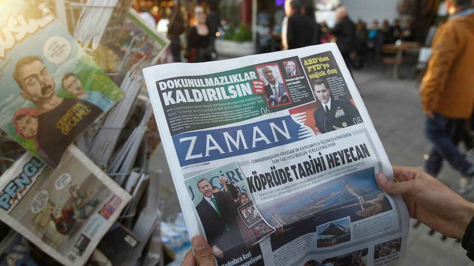 Man reads newspaper Zaman, which has been taken by the Turkish government