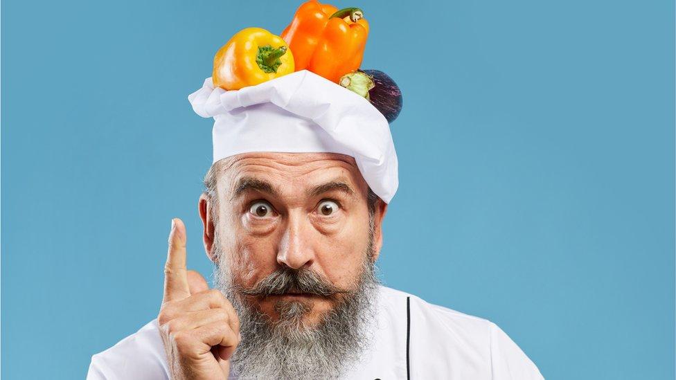Un chef con verduras en su cabeza.