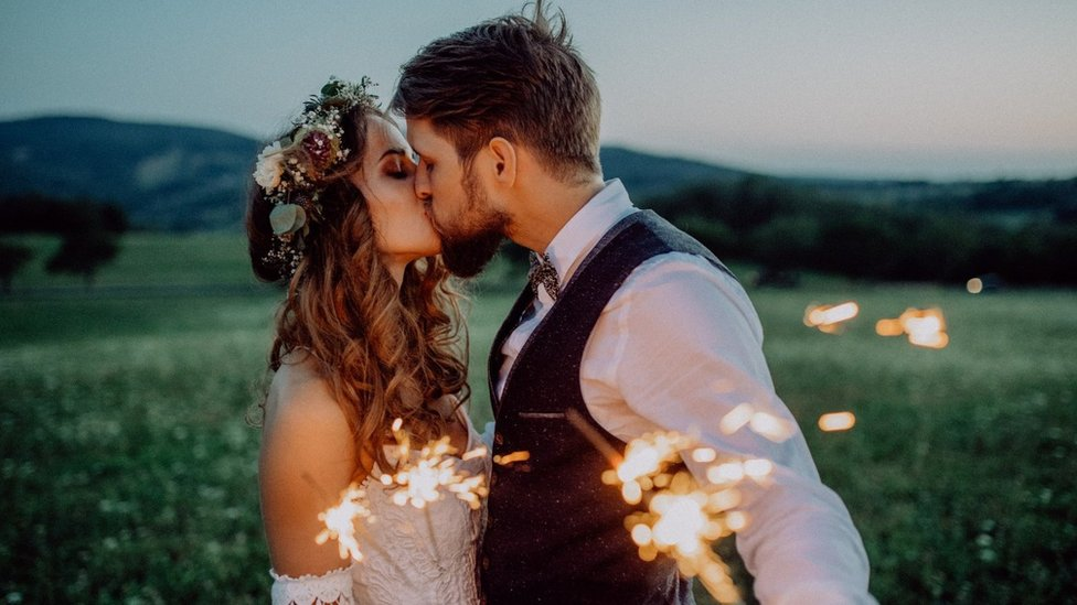 A man and a woman at their wedding holding sparklers in a field
