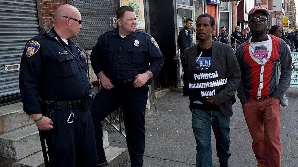 Dos estadounidenses negros caminan frente a dos policías blancos.