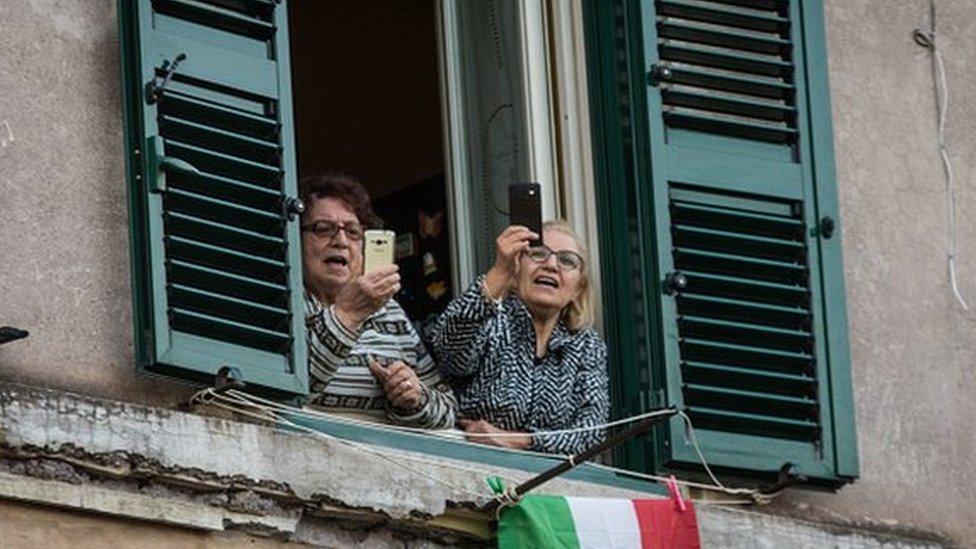 Dos mujeres con sus teléfonos en las manos mientras cantan en el balcón.