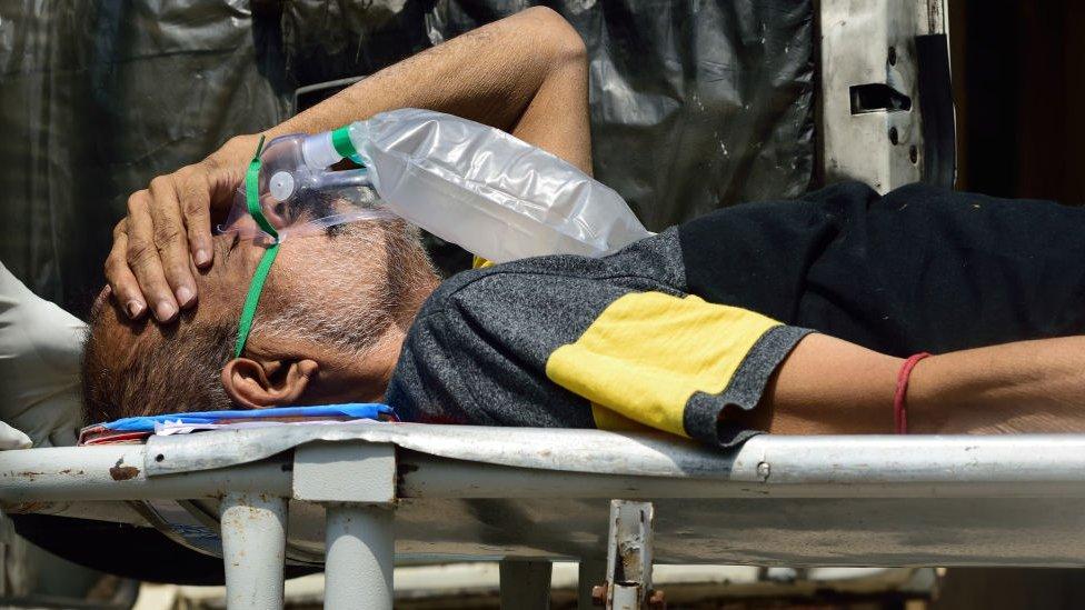 Um paciente de covid-19 usando uma máscara de oxigênio médica sendo carregado em uma maca para um hospital antes da internação em Calcutá, na Índia, em 24 de abril de 2021