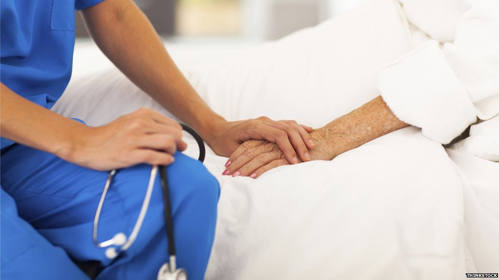 Doctor comforts patient on bed