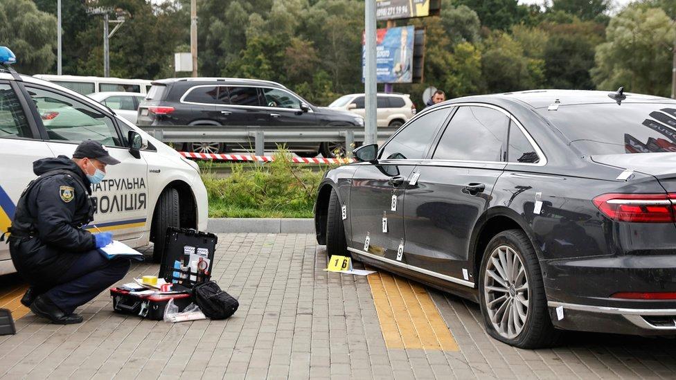 An investigator examines bullet holes in a car of presidential aide Serhiy Shefir following an assault outside Kyiv