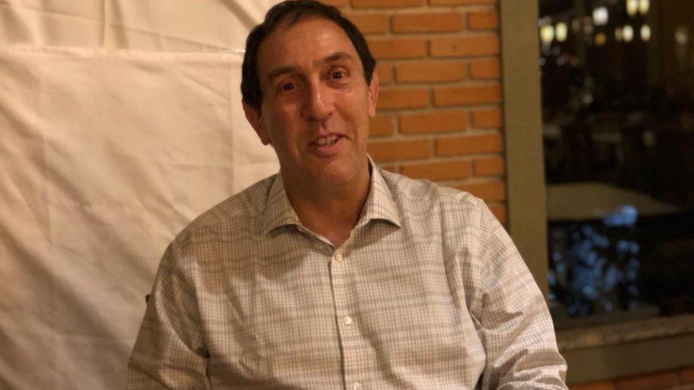 Médico Jaques Sztajnbok dá entrevista em ambiente interno, aparentemente um restaurante
