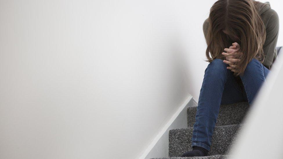 Una mujer sentada en una escalera