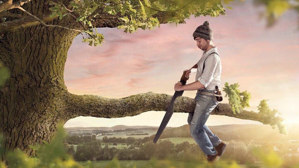 Hombre cortando la rama de un árbol sobre la que está sentado