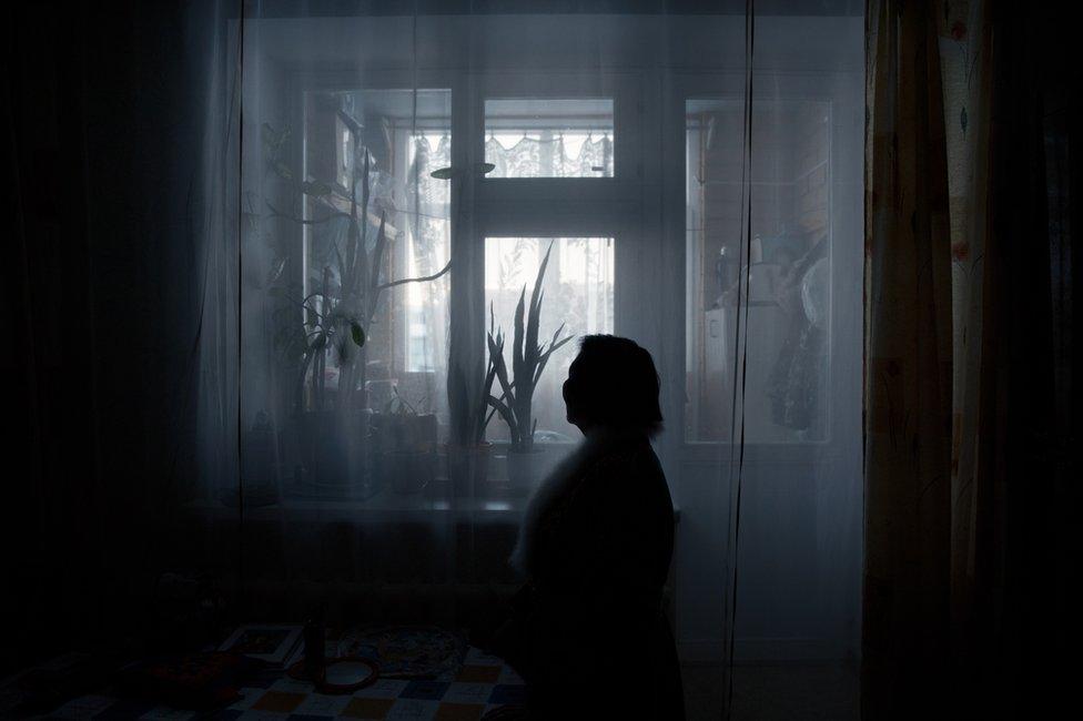 Liliya Yamkina (Born. 1944) looking through the window in her apartment. Yar-Sale village, Yamal Peninsula, Siberia, Russia.