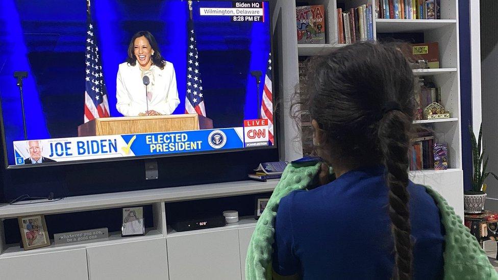 Una niña observa el discurso de Kamala Harris en televisión