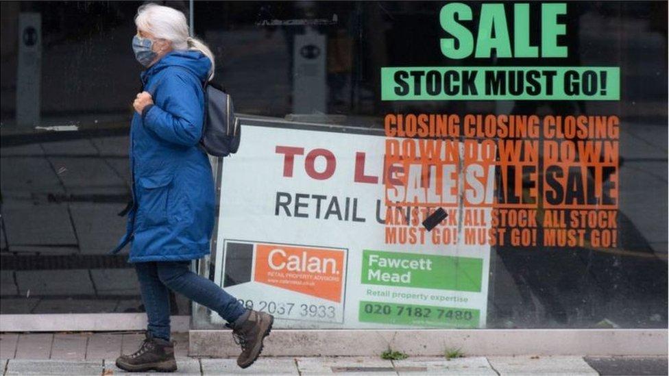 Shopper walking past distressed shop