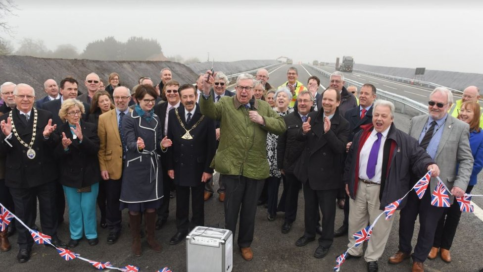 Broadland MP Keith Simpson cuts the ribbon to the final section of road