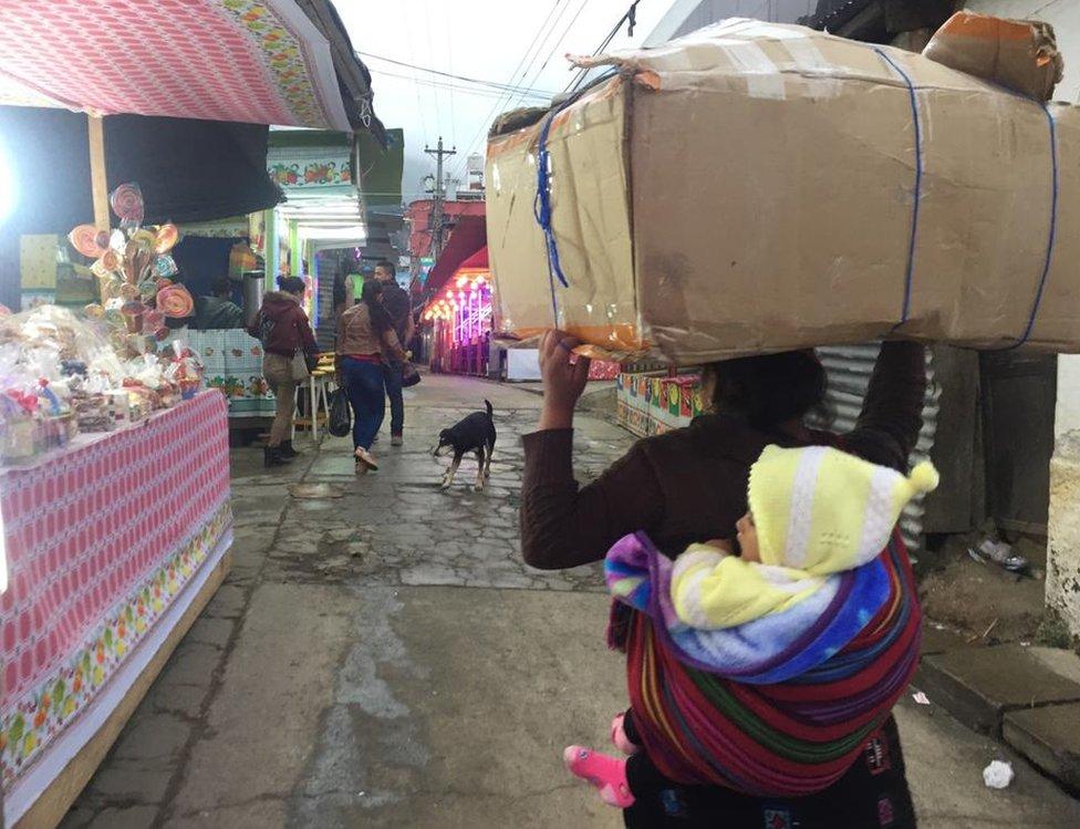 Mujer carga a su hijo en un mercado.