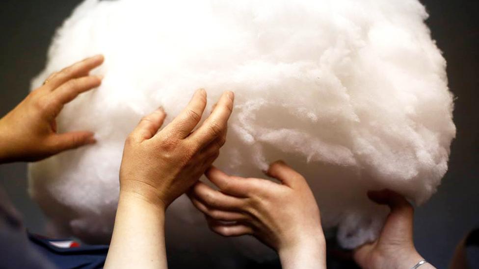 Manos tocando una nebulosa de un material parecido al algodón.