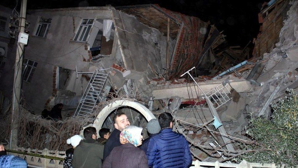 أشخاص يقفون أمام أنقاض مبنى بعد الزلزال في ألازيغ