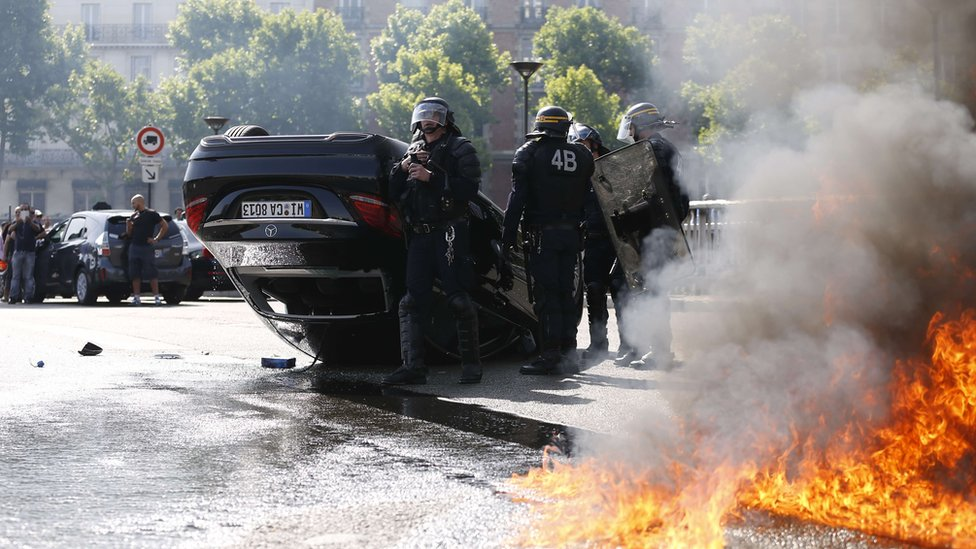 Smoke rises from a fire burning next to French CRS riot police standing near an overturned car as taxi drivers block Porte Maillot in Paris on June 25, 2015.