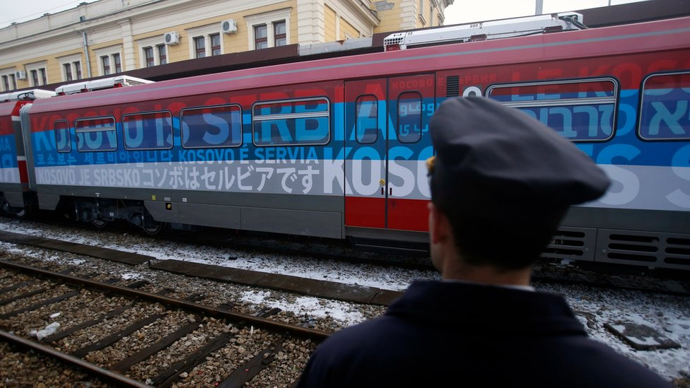 """A railroad worker stands by the first train decorated with letters that read """"Kosovo is Serbian"""" written in twenty languages"""