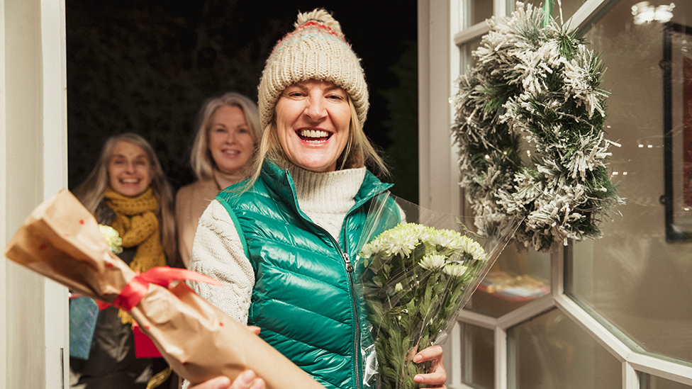 Guests arrive at door bearing Christmas gifts