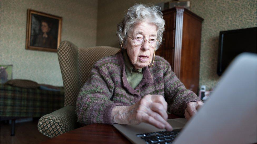 Una mujer mayor con una computadora