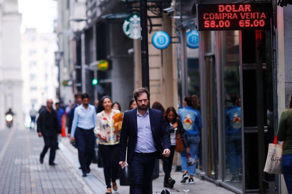 Hombre camina por la calle en Buenos Aires bajo un cartel con el valor de compra y de venta del dólar el 28 de octubre de 2019.