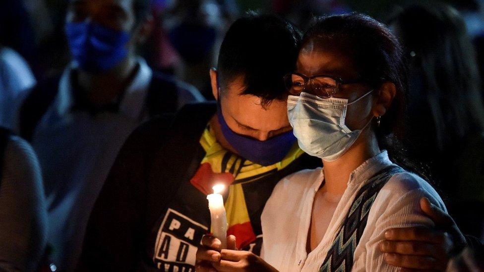 Padres de un muerto en las protestas de Colombia lloran durante una vigilia.