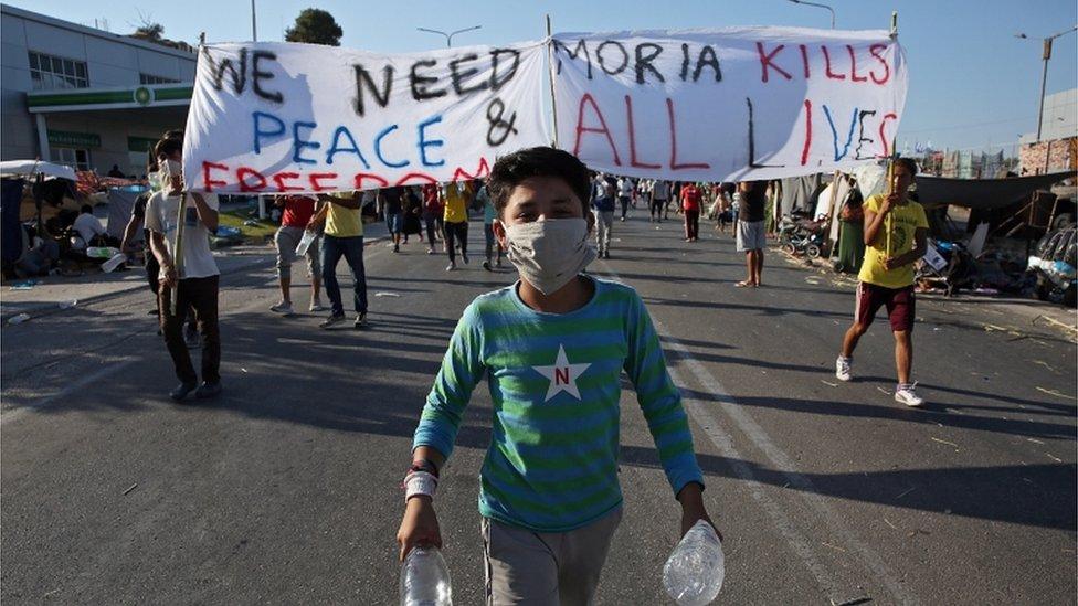 Un niño camina frente al campamento de Moria durante una protesta en Lesbos