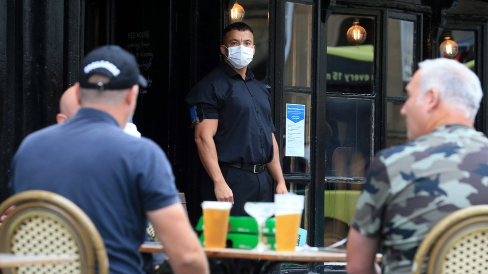 A doorman wearing PPE outside a pub in Newcastle