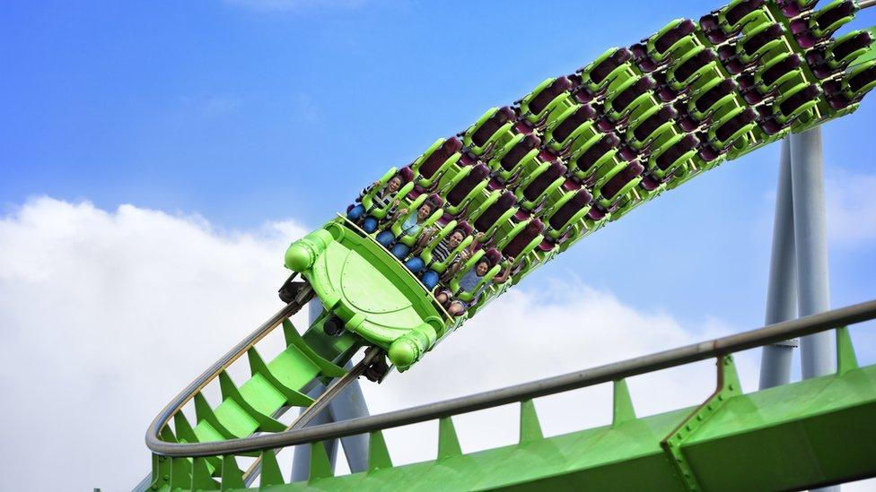 Personas sentadas en la primera fila de la montaña rusa verde mientras gira en una curva