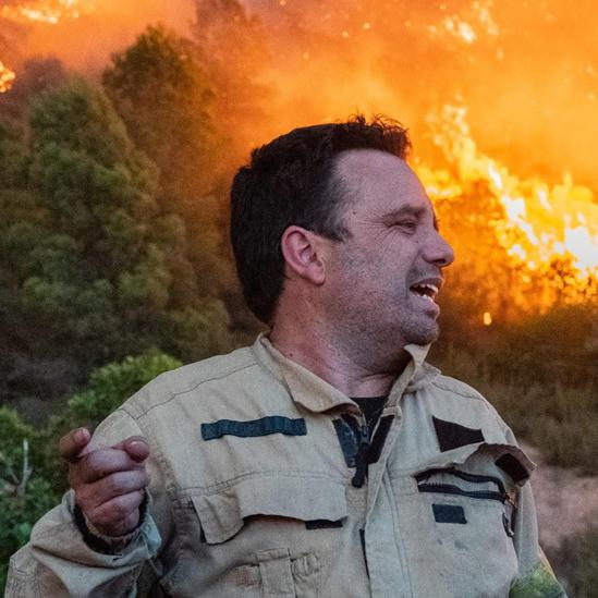 Marc Castellnou con un bosque en llamas de fondo