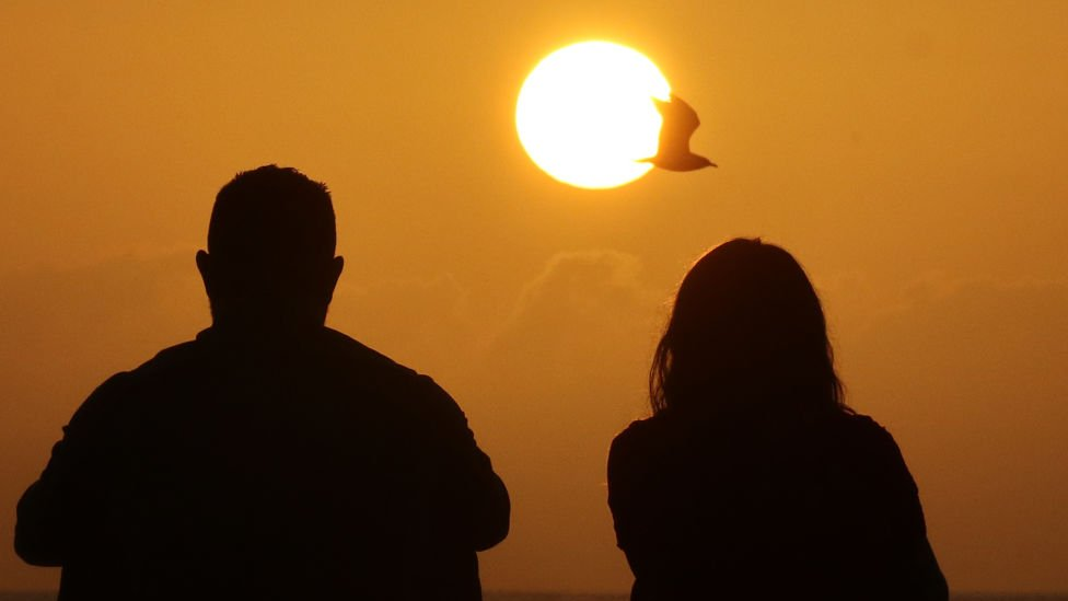 Una pareja frente al sol