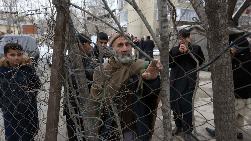 Bystanders with grim expressions watch the aftermath of a suicide attack on the Supreme Court in Kabul, Afghanistan, Tuesday, Feb. 7, 2017