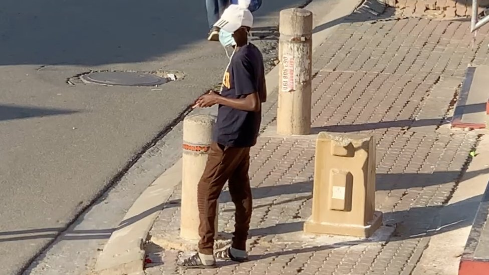 Man waits on a street corner to sell cigarettes