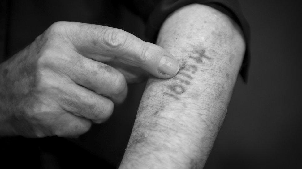 Hombre enseñando el número que le tatuaron en un campo de concentración