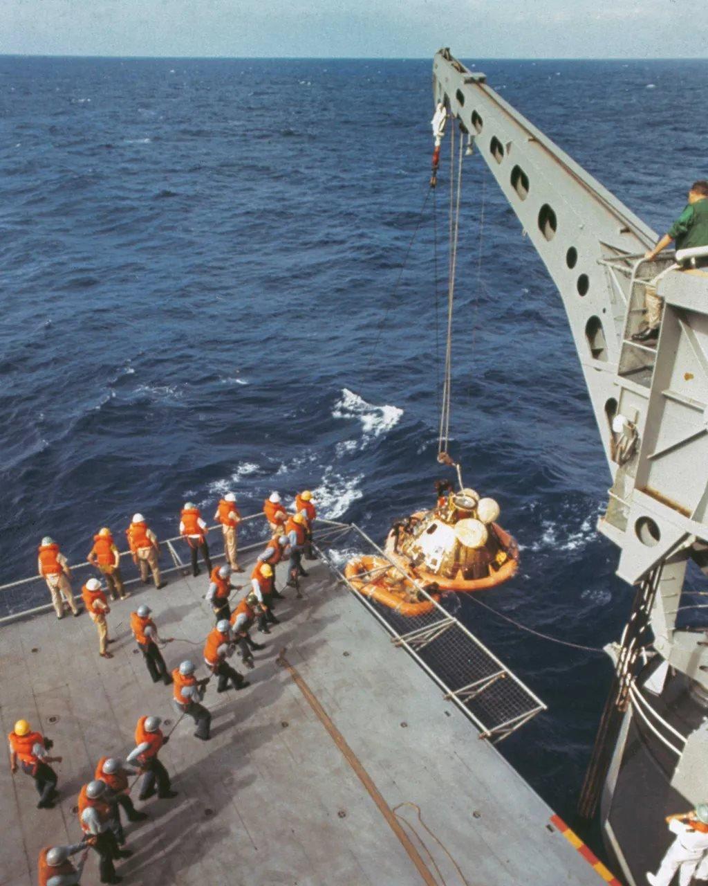一架起重機將阿波羅11號太空艙抬到飛船上,而宇航員已經在飛船上了。