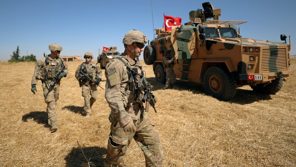 US soldiers walk together during a joint patrol with Turkish forces near Tal Abyad, Syria (8 September 2019)
