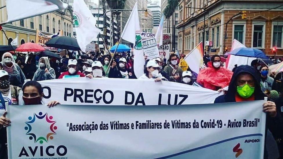 Paola e Gustavo seguram cartaz enquanto outras diversas pessoas protestam e carregam mensagens contra o governo federal